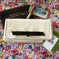 Kate Spade Keira Chelsea Park Clutch Wallet New with tags and dust bag, Kate Spade clutch / wallet. Bone white colored with black bow on front. Interior has the signature bows. Room for the essentials on a night out! Magnetic closure. kate spade Bags