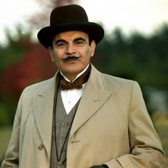 "Poirot filmed in the 1990's wearing a single breasted overcoat with peaked lapels, a grey striped three piece lounge suit, a waistcoat sans lapel, and a stiff fronted shirt with wing collar, bow tie and Homburg hat. From ""COHP""."