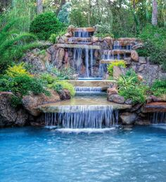 A 20-foot-high cascading waterfall with a two-sided spillway drops into a large spa that flows into a stream leading to the pool.