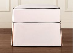 Classic straight skirt ottoman in cream with black piping.