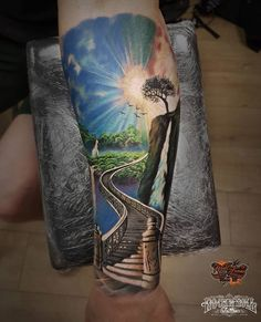 The sun is shining brightly in a blue sky, water spills over a cliff from a high waterfall. A large set of stairs start at the wrist and ascend up the forearm. Tattoo by Marek Hali. Sky Tattoos, Black Tattoos, Cool Tattoos, Amazing Tattoos, Waterfall Tattoo, Scenery Tattoo, Tattoo Collection, Heaven Tattoos, Paradise Tattoo