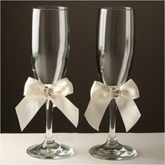 "Toasting Flutes - With This Ring - WeddingDepot.com - 252-K463 Add a special touch to your wedding reception and to your cake table with these toasting glasses.  Set includes two toasting glasses measuring approximately 8.5"".  Each flute is accented with a bow that you can incorporate into your wedding theme.  Bows are available in white or ivory."