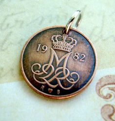 Coin Jewelry Cute 5 Ore Danish COIN NECKLACE Pendant, tiny coin with crown over ornate M monogram, viking celtic design coin. $8.95, via Etsy.