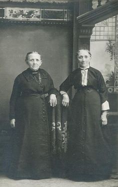 Studio portrait of the Yeatman sisters resting their arms on a piece of draped furniture between them (c. 1893).