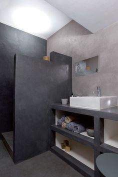 Une douche italienne installée dans une salle de bain entièrement conçue en béton ciré.