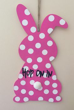 """This adorable wooden hand painted pink bunny with white polka dots would look great on your front door. """"Hop on in"""" is painted across the middle of the bunny to welcome family and friends."""