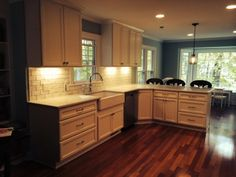 Custom kitchen with wide white cabinets and hardwood floors