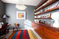 Love the floating wood bookcases and splash of color against grey!