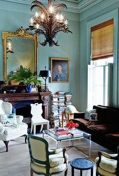 Living room, very eclectic, stacked books, mirror, rattan blinds....