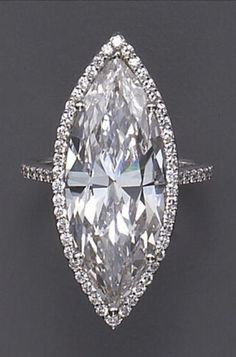A diamond and platinum band with solitaire marquise-cut diamond weighing 10.27 carats frame in round brilliant-cut diamonds