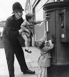 A policeman helps a young child post a letter, London