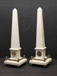 A pair of Grand Tour white marble gilt bronze mounted obelisks, 19th century ; each on rectangular pedestal with square base encircled by chain balustrade, all on toupie feet - Dim: height 19in.