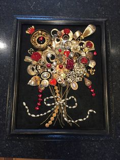 This is a 100 percent handmade recycled jewelry art flower bouquet. First I glue black felt on cardboard backing and then I securely glue the jewelry on the fabric. I use beads, charms, chains, and rhinestones, from necklaces, earrings, bracelets, and brooches. The recycled frame