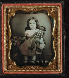 Girl holding a black rag doll, seated beside table with table cloth.  1852