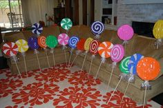 cut out circles from thick insulation board (bought at Lowes). I then painted each one with a different design, sprinkled them with glitter, wrapped them in cellophane and then stuck a dowel rod in them.