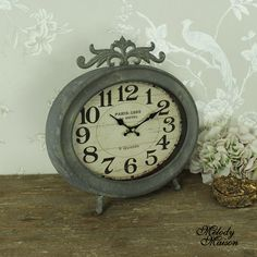 Large Grey Paris Mantel Clock A gorgeous vintage style mantel clock Made from metal with a grey distressed finish With an oval faced and glass front Perfect for a mantel piece or shelf - requires 1 x AA battery