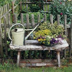 Bench with watering can and flowers