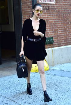 Out in NYC wearing a black belted mini dress, black patent leather booties, and a black leather duffle bag.