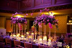 Tall acrylic stands held full, elongated floral pieces with bold arches made of curly willow and accented with orchids. The ballroom boasts a beautifully detailed 30 foot ceiling, so it was important to use elements which drew the eye upwards. Dozens of floating candles decorated the tabletop and added a luminescent glow to the room.