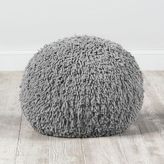 Shop Shaggy Pouf (Grey).  Originally, we were going to give this grey shaggy pouf a haircut, but we wanted it to express itself (and we thought it looked good with a long pile).  Its soft chenille cover makes it both stylish and comfy.