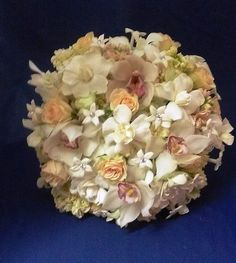 This fragrant bouquet showcases white flowers, including gardenias, dendrobium orchids, hydrangea, stock, and stephanotis, the traditional wedding flower, studded with rhinestone centers. Peach roses and cymbidium orchids with a touch of purple add a touch of color.  See more wedding bouquets, centerpieces, and more at www.jeffmartinsweddings.com