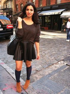 Racheal Sarah School girl chic in Soho with a leather skirt, knee high socks, a grey sweater, and booties.