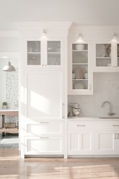 simons hardware Traditional Kitchen Remodelling ideas New York Built-in refrigerator with panels down lights glass cabinet doors marble backsplash mixer nickel hardware shaker spotlights traditional Traditional Kitchen with a modern flair undermount sink white cabinets white counters wood floor