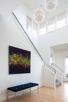 Clean, hard lines create a sophisticated, modern look in this stunning entryway. Three gorgeous pendants hang show off beautiful high ceilings with original crown molding. A navy velvet bench set under a gorgeous multicolor painting completes the elegant tone.