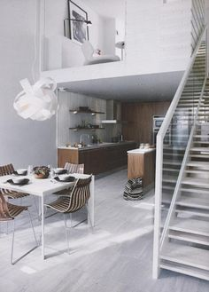 Nice, white contemporary space with wooden kitchen adding texture and colour matching dining chairs.