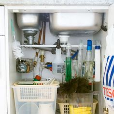 se a curtain rod and baskets to organize under your sink