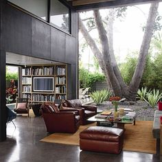 The living room, with its rich brown concrete flooring and smooth steel panelling, opens on to a courtyard with a huge sculpture in the form of an Aleppo Pine tree.