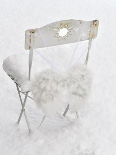 Angel wings on the back of a chair. How cute of an idea for a wedding to honor those who have passed and could not share the day with you!