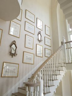 Amazing staircase art gallery with ivory walls paint color, gold leaf frames and antique sconces.