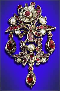 a pinchbeck brooch from mid-eighteenth-century England is an openwork floral spray whose leaves are set with half pearls and garnets. - Photo by Tom Green