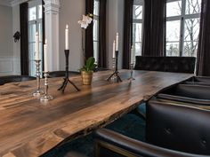 A rustic, rough-hewn slab dining table brings a splash of nature to this elegant, eclectic dining room. A pretty centerpiece comprised of silver candlesticks and a potted orchid adorns the table, counterbalancing the rusticity of the slab.
