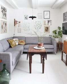 Love the light gray couch and the staggered picture frames. Also like the wood table.