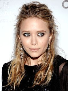 Mary-Kate Olsen neatly pins back the top of her lustrous yet tousled hair.