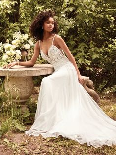 Rebecca Ingram - SERAPHINA, This romantic boho wedding dress features a sheer bodice accented in floral lace motifs over a Santorini chiffon A-line skirt. Lace trim spaghetti straps glide from V-back to illusion plunging neckline in a unique crisscross effect. Finished with covered buttons over zipper closure.  Available in plus size.