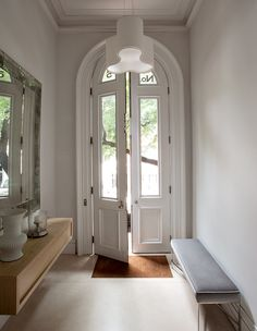 This entry's extra-tall arched doors are typical of New York's prettiest mid- to late-19th-century rowhouses and make a formidable first impression.   Photographer: Matthew Williams Design: Lucien Rees Roberts