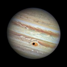 An image taken by the Hubble Space Telescope shows the shadow of the Jovian moon Ganymede in the center of the Great Red Spot. At the time of the photo, Hubble was being used to monitor changes in Jupiter's immense Great Red Spot (GRS) storm.