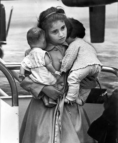 Vintage photo of a young Cuban girl, a refugee bringing her dolls to Miami in