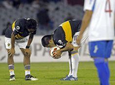 Riquelme besa la pelota y Erviti lo mira.