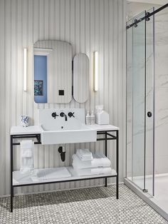 The spa-like bathroom features marble tile and a freestanding vanity.