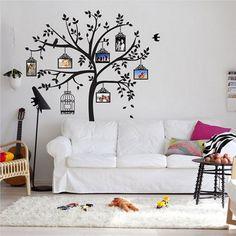 Sala de estar bem simples que ganhou um up a mais na decoração com um lindo adesivo de parede em forma de árvore com gaiolas penduradas. Os adesivos de parede são ótimos para dar cor ao ambiente ou quebrar decorações muito monótonas. O toque de cor ficou por conta da almofada em cor magenta.
