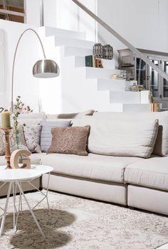 Landelijke woonkamer met moderne accenten. Zitmeubel Ravenia, karpet Patchwork, vloerlamp Bow. Goossens wonen & slapen