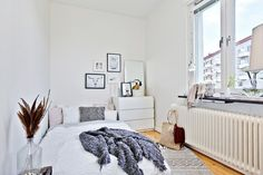Small light space. Great example of a cozy urban bedroom: white bedding, white dresser, cute frame arrangement.
