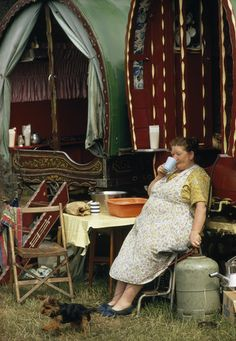 Elderly gypsy woman drinks tea at table near her bow-topped wagon.  Location:Appleby, England.  Photographer:BRUCE DALE/National Geographic Stock