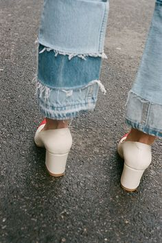 Distressed hem jeans and white heels