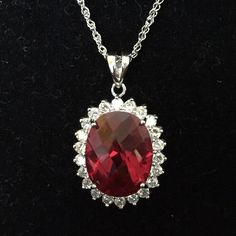 """Sterling Silver (925) Large CZ Ruby Necklace Large CZ ruby, surrounded by small, clear CZ stones and set in 925 sterling silver. Pendant measures 1.50 inches and is marked """"GWE 925 CZ"""". Sterling silver chain is 18 inches and marked """"925 AV"""". Jewelry Necklaces"""
