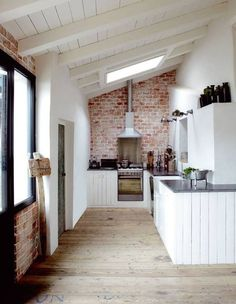 Small space kitchen...Roofline, exposed brick wall, white painted timber ceiling